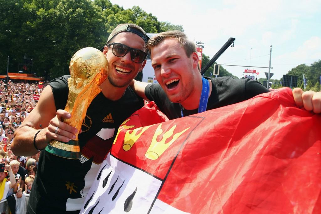 In Berlin feierte Lukas Podolski mit WM-Pokal, Köln-Fahne und Kevin Großkreutz Foto: IMAGO