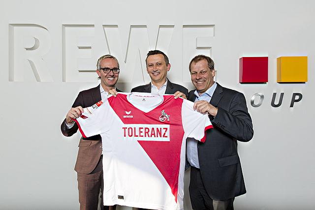 Das entsprechende Trikot überreichten FC-Geschäftsführer Alexander Wehrle (l.) und FC-Vizepräsident Markus Ritterbach jetzt an Lionel Souque (Mitte), Vorstandsmitglied REWE Group. Foto: Thomas Fähnrich / 1. FC Köln