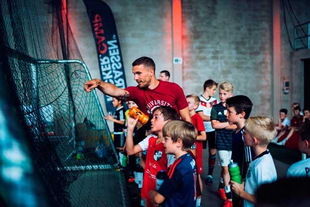 Zusammen mit den Kids verfolgt Lukas Podolski die Spiele bei seinem Strassenkicker.Cup.