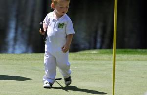 Ein kleines Kind steht auf einem Golfplatz